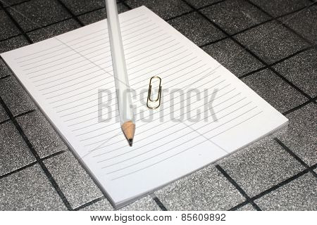 paper clip, pencil and paper