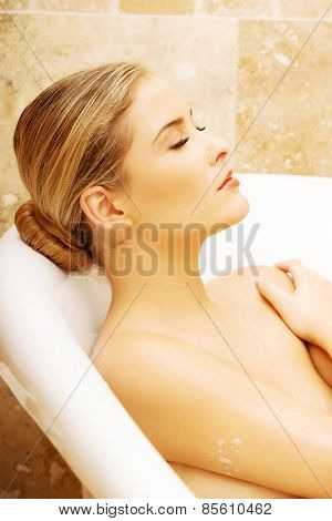 Portrait of a woman relaxing in bathtub with her eyes closed.