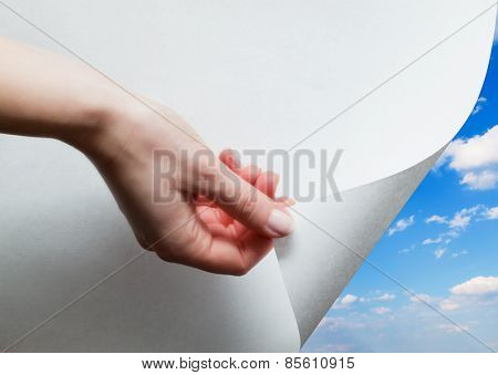 Hand pulling a bottom paper corner to uncover, reveal sunny blue sky. Page curl, conceptual.