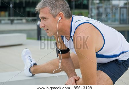 Mature Male Athlete Exercising And Listening To Music In The City