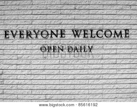 Detail of a sign saying everyone welcome on white brick wall