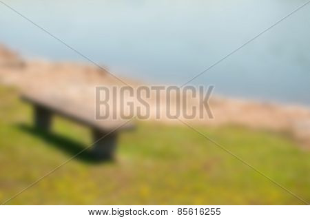 Abstract blurred background with a bench at lakefront facing water