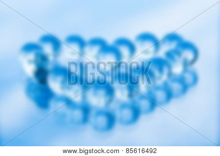 Blurred abstract background of glass balls in shape of heart, in blue