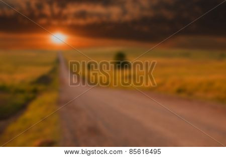 Blurred background image of dramatic sunset over a rural road