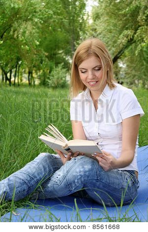 Portrait Of Young Blonde Woman Reading Book In The  Park