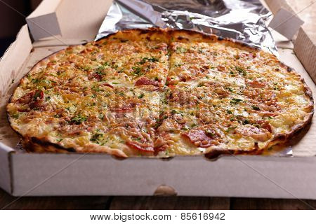Tasty pizza in box on wooden background
