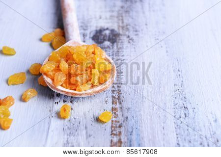 Raisins in spoon on color wooden table background