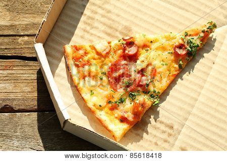 Last slice of pizza on wooden table