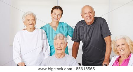 Happy group of senior citizens in nursing home with geriatric nurse