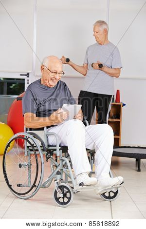 Elderly man in wheelchair reading ebook with tablet computer in a nursing home
