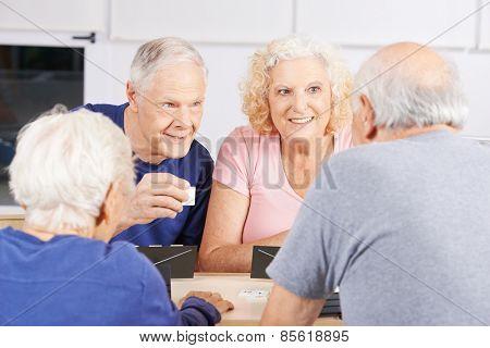 Group of senior people playing rummikub game in a nursing home