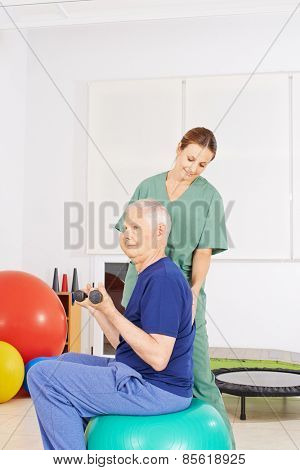 Old man with dumbbells on gym ball in a physical therapy praxis