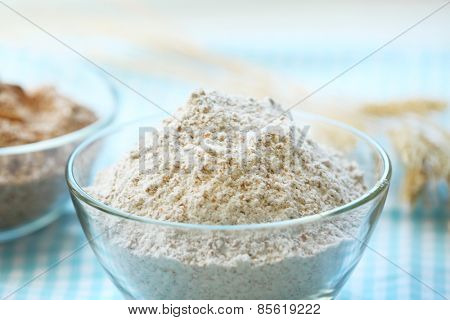 Glass bowls of flour with wheat on squared tablecloth background