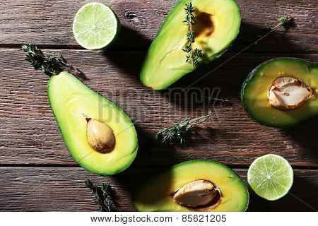 Sliced avocado with herb and lime on wooden background
