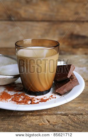 Glass of milk with chocolate chunks and cocoa on rustic wooden planks background