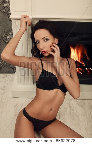 Sexy Brunette Woman Near Fireplace Posing On Vintage Wall