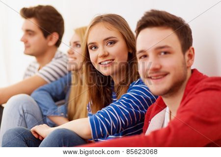 Group of four young people indoors, selective focus
