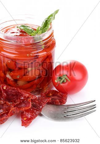 Sun dried tomatoes in glass jar and fresh tomatoes with basil leaves isolated on white