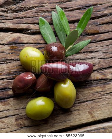 Olive twig and olives on old wooden table.