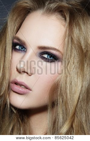 Close-up portrait of young beautiful blonde woman with smoky eyes make-up