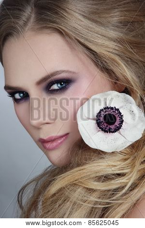 Close-up portrait of young beautiful blonde girl with stylish violet smoky eyes make-up and messy hairdo