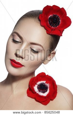 Portrait of young beautiful woman with clean make-up, red lips and red flowers over white background