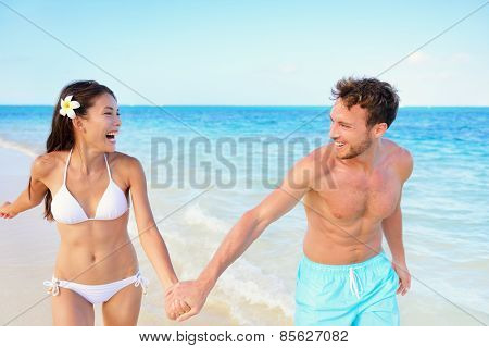 Beach couple having fun happy on beach vacation during summer holiday. Multiracial fit couple running together holding hands laughing in the sun. Young adults in shape carefree happiness.