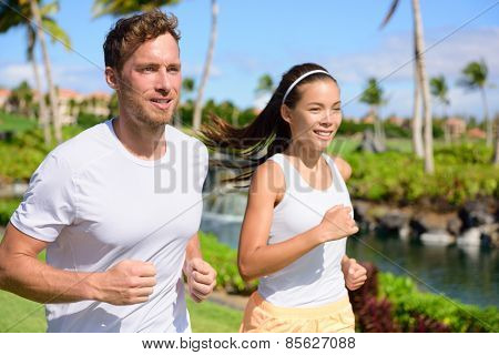 Jogging couple of runners running together in park. Active summer lifestyle, two young adults joggers cardio training in city park or street living healthy.