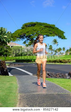 Jogger woman running on sidewalk in city street. Asian mixed race female adult runner in upscale residential neighborhood jogging along the street keeping a healthy lifestyle by exercising cardio.