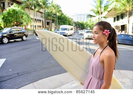 Urban surfer Asian girl holding surf board walking in city going surfing in Waikiki beach, Honolulu, Oahu, Hawaii, USA. Woman waiting for street traffic carrying surfboard and wearing Hawaiian flower.