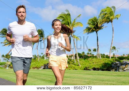 People running in city park. Happy young couple living an active healthy lifestyle jogging training their cardio during summer on road or neighborhood street. Multiracial group, Asian and Caucasian.