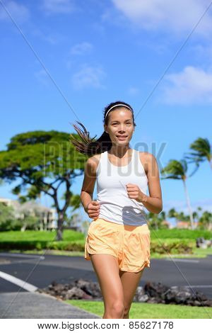 Young woman jogging on city street during summer. Asian girl doing cardio exercise training the body to lose weight and staying fit and in shape. Portrait waist up of female jogger going for a run.