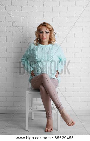Young pregnant woman sitting on chair on light background