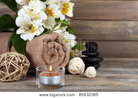 Beautiful spa composition with candle and flowers on wooden background