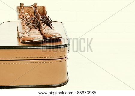 Vintage suitcase with male shoes on light background