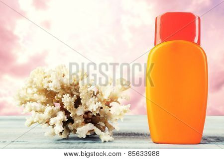 Bottle of suntan cream with coral on table isolated on white