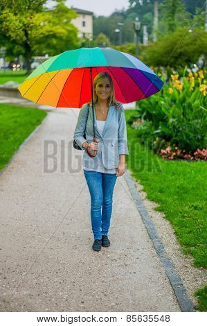 a young woman walks with a colorful umbrella in hand walking in the rain.