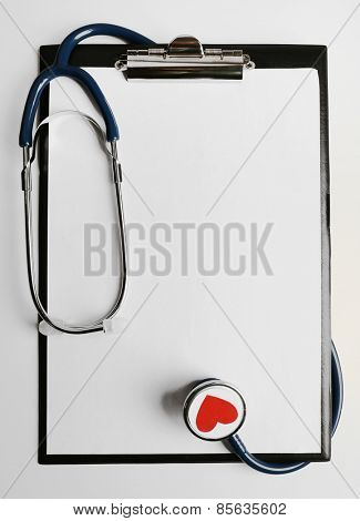 Stethoscope with tablet for notes on light background