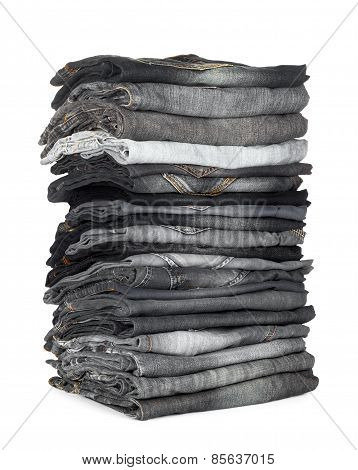 High Stack Of Jeans Gray And Black On A White Background
