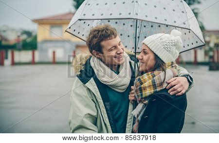 Young Couple Embracing And Laughing Outdoors Under Umbrella