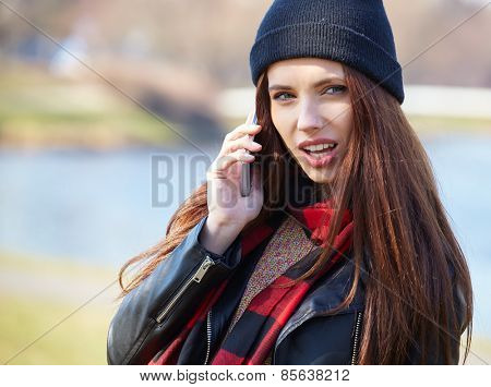Portrait of pretty girl outdoor, wearing a cap talking on a cell phone
