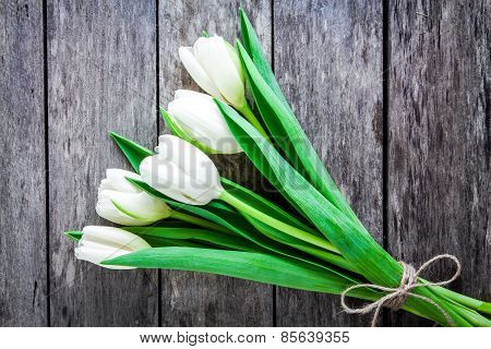 Bouquet Of White Tulips On A Rustic Background