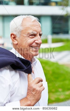 Happy old businessman smiling in summer in the city