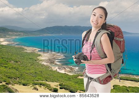 Happy smiling Asian young female backpacker with camera standing in front of beach of Kenting, Taiwan, Asia.