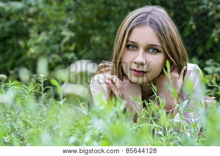 portrait of the beautiful girl in a grass