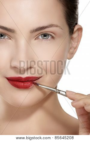 Beauty Model Applying Red Lipstick With Brush