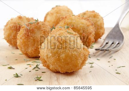 Fried Potato Balls With Thyme And Fork