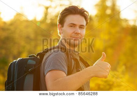 Young man tourist with backpack showing thumbs up handsign. Red sunset light.