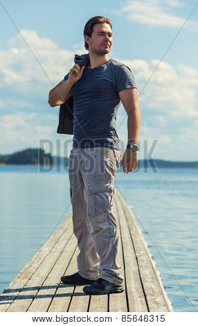 Young man standing on wooden bridge and looking aside