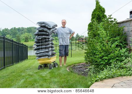 Man Standing Beside A Wagon With Bagged Mulch